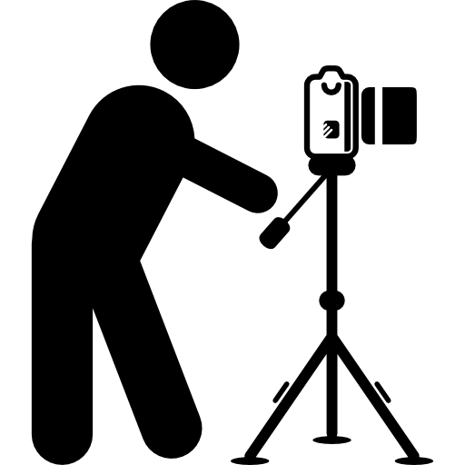 photographer standing behind photo camera on a tripod from side view